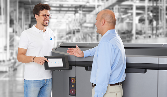 Two men discussing HP Jet Fusion 4200 3D Printing Solutions in front of printer