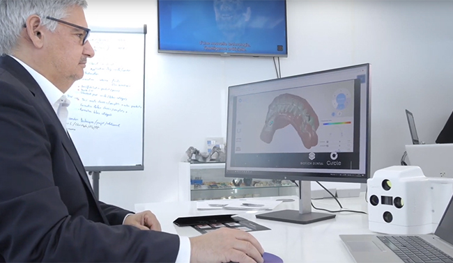 Man viewing dental prototype on computer