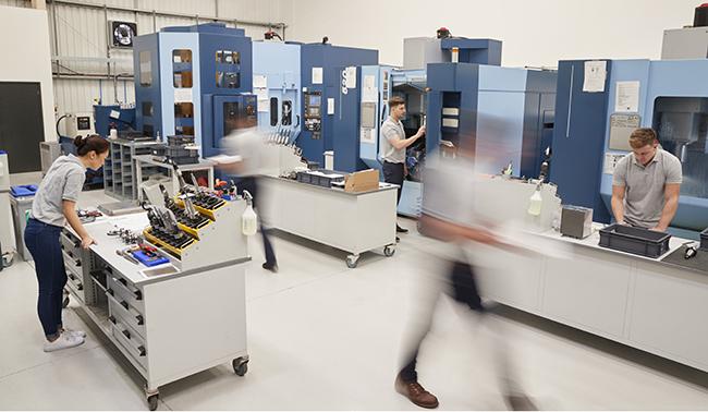 Machine shop floor with people working
