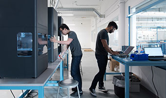 Two men working on Markforged printers